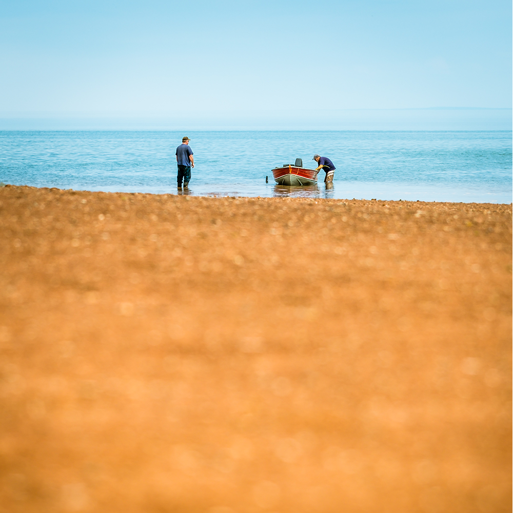 two men standing near a boat in the shallow water just off a beach