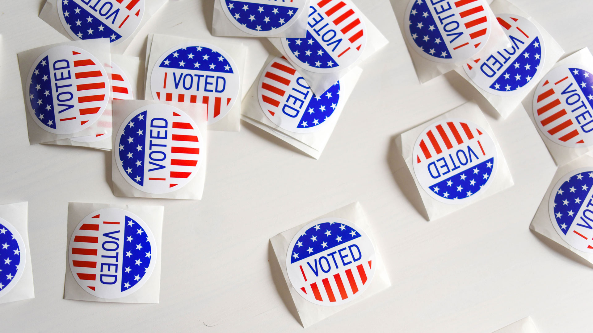 "Several ""I Voted"" stickers haphazardly arranged on a white background"